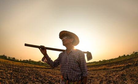 Elderly Asian farmers shoveling and prepare the soil with a spade for planting on sunset background. Archivio Fotografico