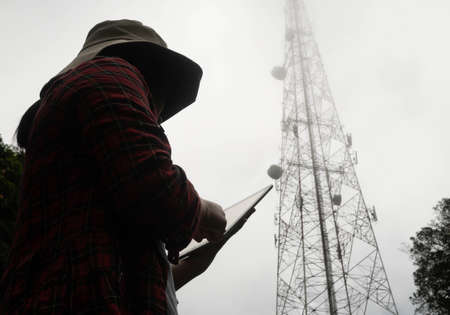 Female engineer using tablet computer checking the frequency with telecommunication towers with TV antennas and satellite dish In the foggy morning.