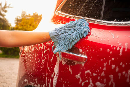 Close up of hand is washing car by mitt with bubbles soap outdoors. Zdjęcie Seryjne