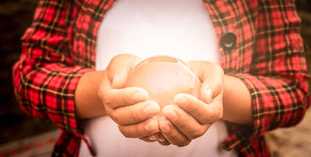 Asian woman holding a magic crystal glass ball in her hands.