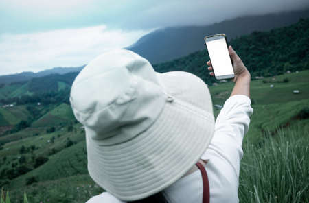 Tourist enjoy nature and take pictures with smartphone on the mountain background. Zdjęcie Seryjne