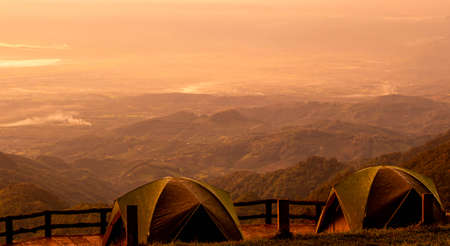 Two tents stands against the background of beautiful mountain landscape with the warm sunset light. Zdjęcie Seryjne