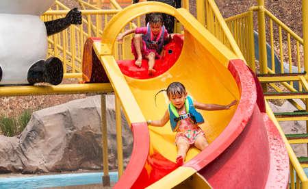 Happy siblings girls playing slide in outdoor swimming pool.