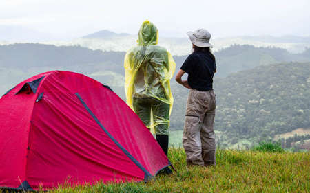 Couple stand at tent and enjoying the beautiful foggy mornig on the mountain top. Doi Mae Tho, Chiang Mai, Thailand.