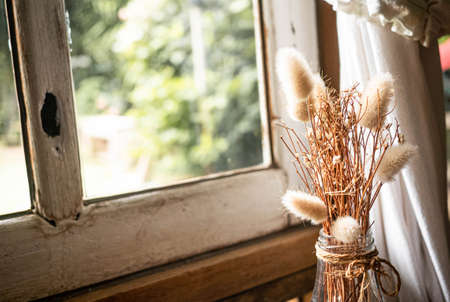 Dried flowers in a glass bottle on wooden table by the window with the sunshine coming in the room. Living room decoration.