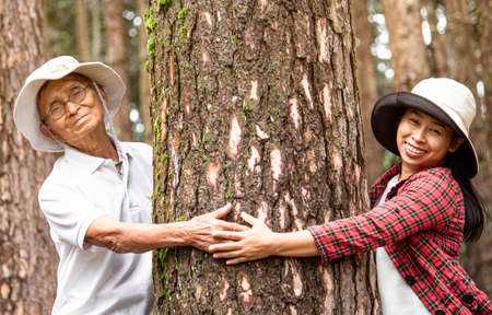 An adult daughter with senior father hugging a tree in the woods. Earth's day concept with people protecting the trees from deforestation.