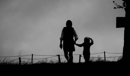 The silhouette of mother holding her daughter's hand walking on lawn in the park.