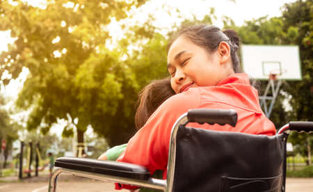 Happy mother in a wheelchair hugging little girl sitting on her lap in the park. Disabled, motherhood concept. Zdjęcie Seryjne