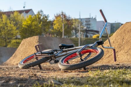 BMX bike on the track with jumps on the background with houses. Jumping track for bicycles in the city.