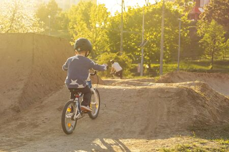 Kid riding a bike. Sunny summer day. Child on a bicycle at pump track. Active kid.