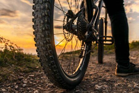 Mountain bike tire. Mountain bike rear wheel detail. Back shot of mountain bike on sunset.