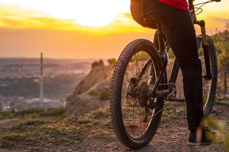 Back shot of mountain biker at sunset sitting on a modern off-road bike on the hill. Banque d'images