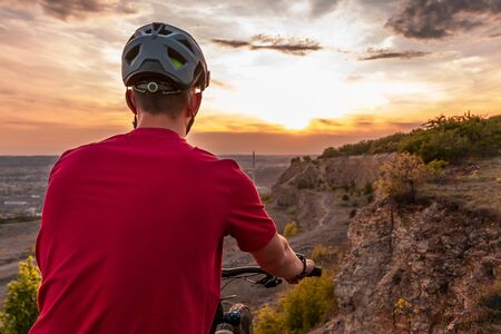 Mountain biker at sunset with modern bicycle helmet.