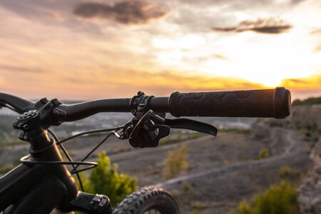 Detail of bicycle handlebar grip. Mountain bikes at sunset.