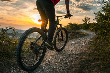 Back shot of mountain biker at sunset sitting on a modern off-road bike on the hill behind the city. Stock Photo