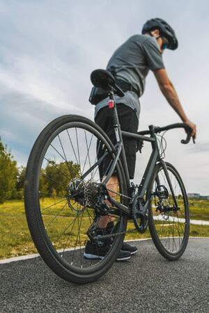 Vertical shot of cyclist with a road bike on the asphalt bicycle path. Close up shot of the rear wheel. Stock Photo