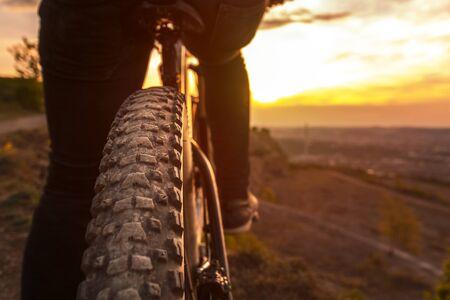 Back shot of mountain bike on sunset. Mountain bike rear wheel detail. Mountain bike tire.