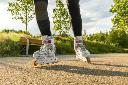 Womans legs with roller blades at sunny day. Close-up shot of white Inline skates on the path.