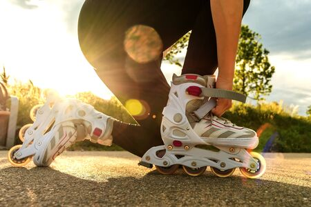 A woman tightens roller skates on the path. Womans legs with roller blades at sunny day.