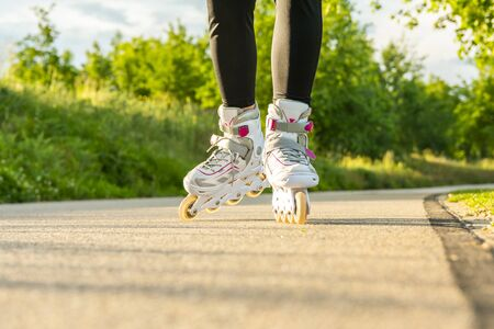 Womans legs with white roller blades at sunny day on asphalt road.