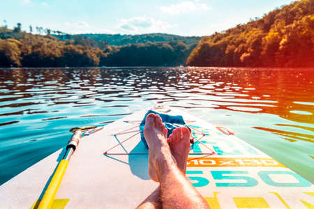 Mens feet on a paddleboard. First person view. Close-up of legs on surf. Relax and travel on the lake at hot summer day. Banco de Imagens