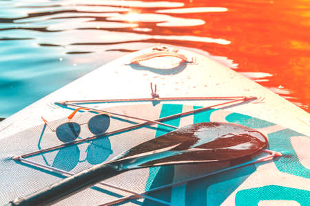 Fashion sunglasses on a paddleboard surf. Relax and travel. Hot summer day. Water sports. Vacation at sea. Banco de Imagens