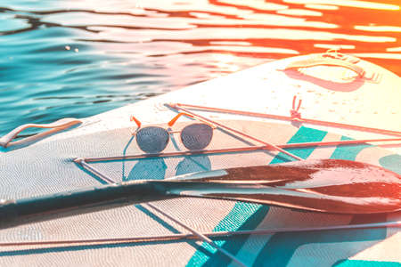 Relax and travel. Hot summer day. Water sports. Vacation at sea.Fashion sunglasses on a paddleboard surf. Banco de Imagens