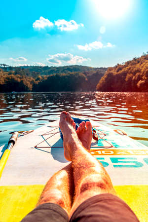 Man relaxing on a paddleboard surf in hot sunny day. Vertical shot. First person view. Close-up of feet on surf. Banco de Imagens