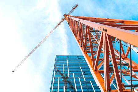 Yellow tower crane. Bottom view of a tall construction crane next to a modern building.