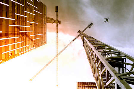 Tower crane. Bottom view of a tall construction cranes next to a modern building. Engineering and architecture design background Banco de Imagens