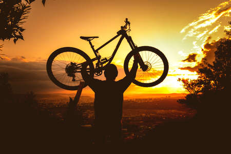 Silhouette of a mountain biker holding a bicycle over his head at sunset. MTB, enduro, freeride background.
