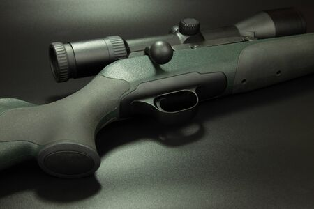 Rifle for hunting with a telescopic sight, black background.