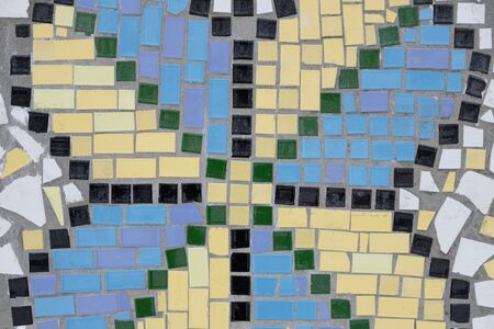 Mosaic image of a butterfly on the wall of a house made of small Spanish tiles. Stock Photo, close up.