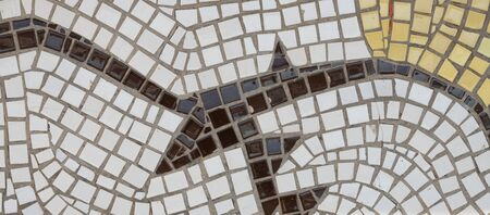 Fragment of a wall lined with mosaic tiles. Abstract drawing. White, brown, beige colored tiles.