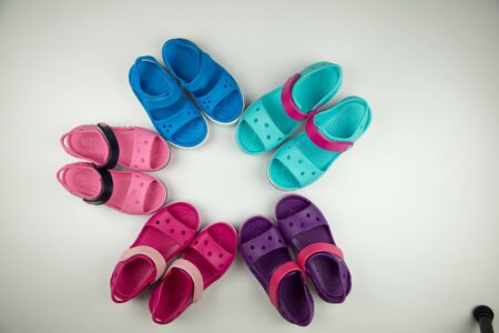 Children's shoes for the beach and leisure on a white background.Top view, different colors.