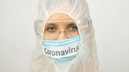face of a white woman in a medical mask - inscription coronavirus, safety glasses and a suit Archivio Fotografico