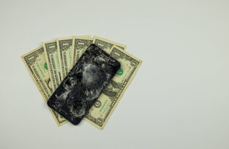 badly broken black smartphone, one dollar bills on a white background, top view Фото со стока