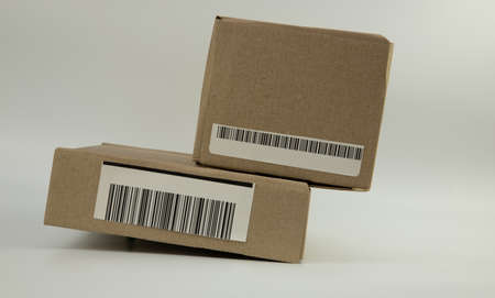 two cardboard boxes with barcodes on a white background Stock Photo