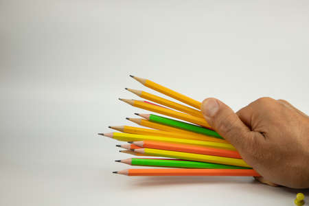 many colored pencils in a man's hand on a white background, close-up horizontal photo, right side of the image Archivio Fotografico