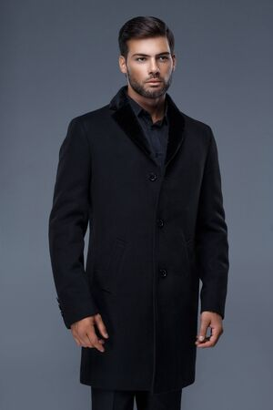handsome sexy man with a trendy haircut in black coat,black shirt