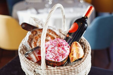 Colorful easter in a basket with, red wine, jamon or jerky and dry smoked sausage on a wooden table