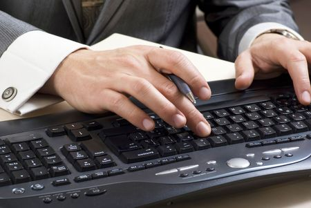 Close-up of male hands touching buttons of black computer keyboard