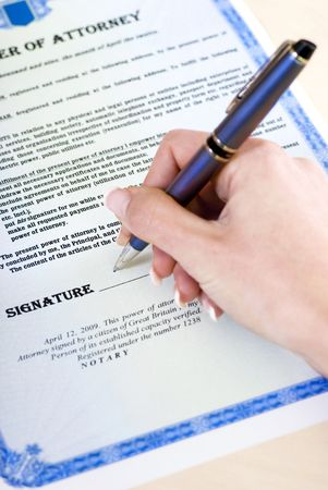 legal document: close-up of a womans hand signing a power of attorney Stock Photo