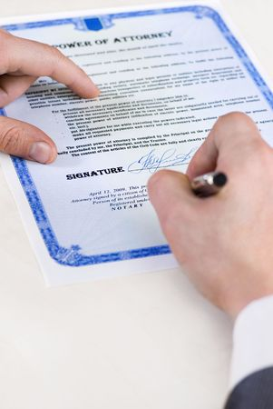 notary signing a power of attorney, focus is on the tip of the pen photo