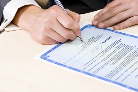 legal document: notary signing a power of attorney, focus is on the tip of the pen