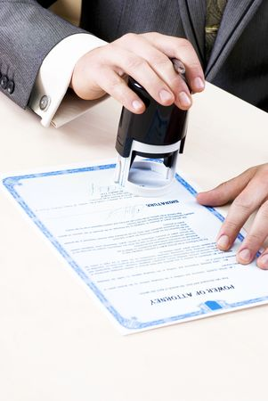 certify: close-up of male hands of the notary stamp on the power of attorney