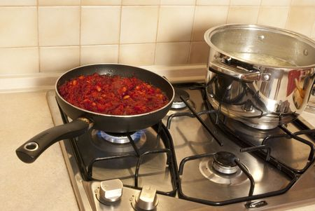 Cooking dinner. On the stove a pot of soup and pan with vegetables