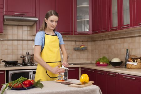A pretty young woman cutting vegetables in a kitchen photo