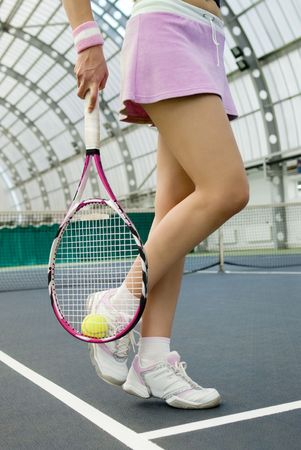 tennis skirt: legs of young girl in a closed tennis court with ball and racket Stock Photo