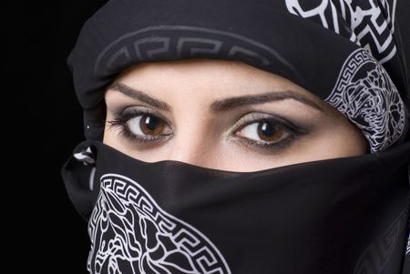 The beautiful brown eyes of an arabic woman with headscarf looking to camera. Focus on right eye.